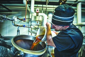 UNITED STATES - December 7, 2015: Nassim Sultan adds honey from Loudoun to a batch of root beer at Lost Rhino Brewing Company in Ashbury Virginia.  The brewery sits in the eastern part of Loudoun County Virginia and uses all locally harvested ingredients and also uses a really innovative technique of cultivating wild Virginia yeast strains from nearby orchards, meadows, and even fossils! (Photo By Douglas Graham/Loudoun Now)