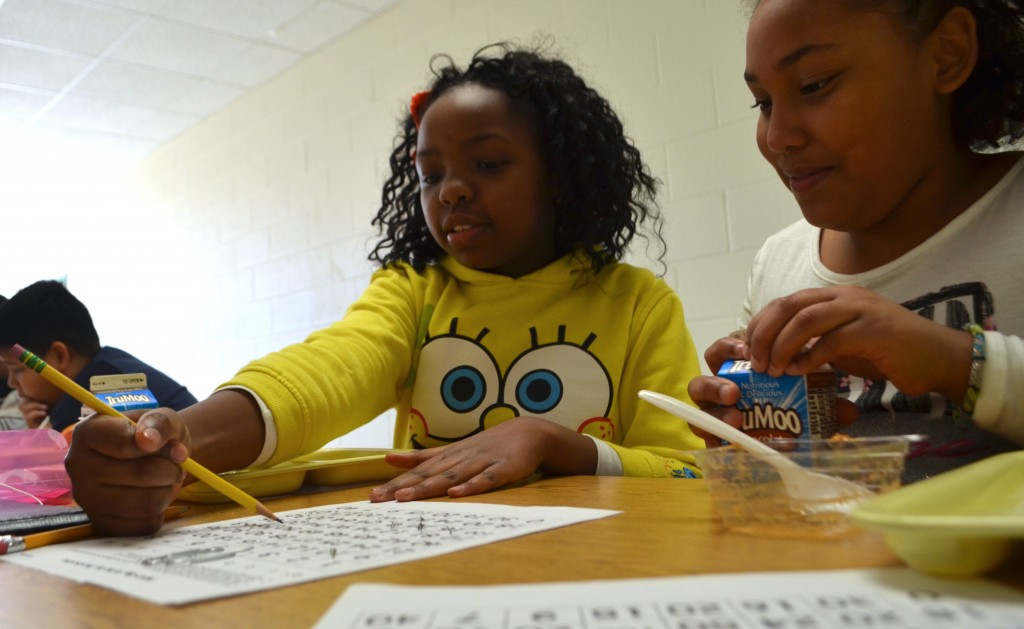 Fourth-graders Daniellah and Sa'Nali play math-themed Bingo with their study buddy, Kaitlin McClymont, a development engineer at K2M. (Danielle Nadler/Loudoun Now)