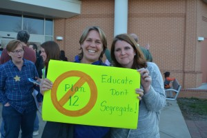 "Gretchen Falter and Anna Peach hold up a sign opposing the school board's ""Plan 12"" after the meeting. (Renss Greene/Loudoun Now)"