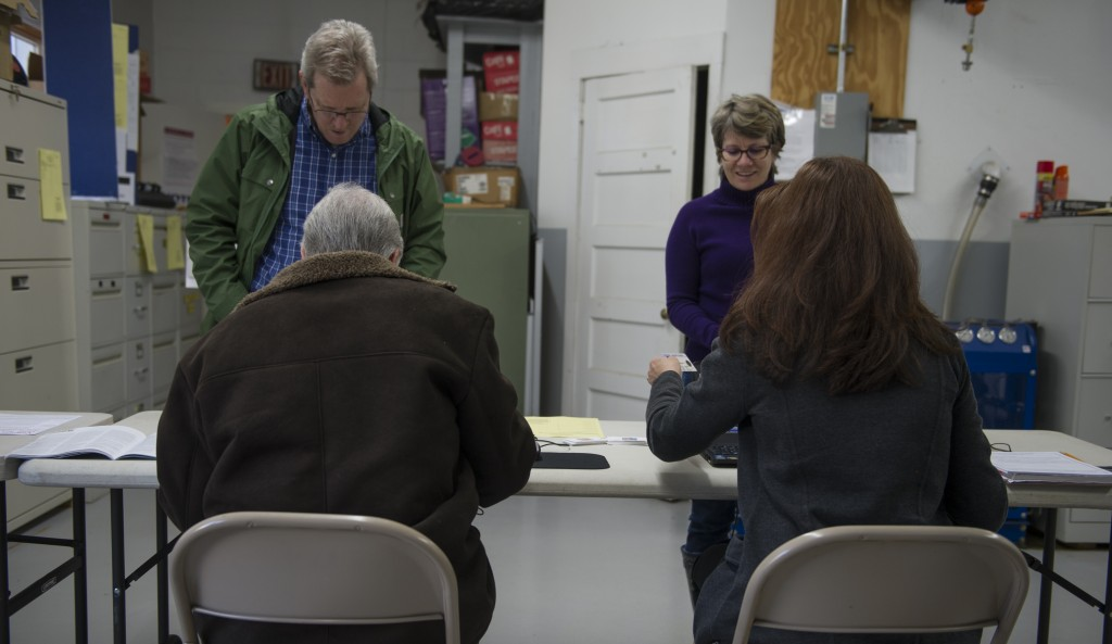 Poll workers (back to camera) Lisa and Terry O'Neill help voters at the Philomont Firehouse during Super Tuesday voting. (Douglas Graham/Loudoun Now)